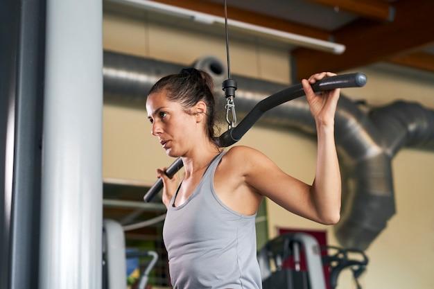 Kobieta w sportowych spodenkach i szarym podkoszulku uprawiająca fitness na siłowni ściska dłonie na specjalnym symulatorze