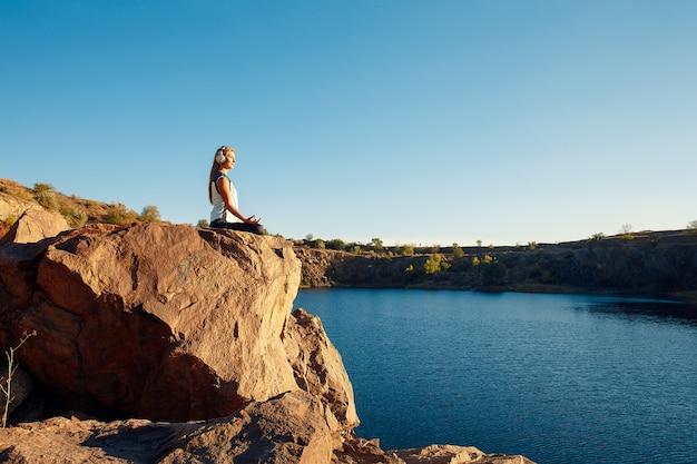 Kobieta w sportowym garniturze i słuchawkach siedząc w pozycji lotosu na skale nad morzem, medytując, słuchaj muzyki. yoga outdoor.