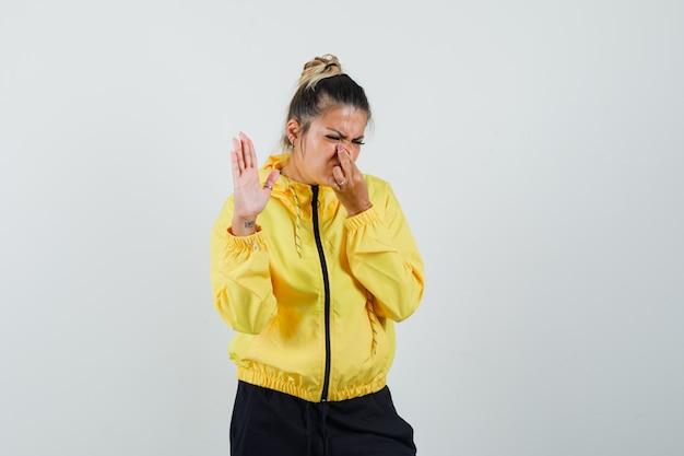 Kobieta w sportowym garniturze szczypie nos z powodu nieprzyjemnego zapachu i wygląda na zniesmaczoną, widok z przodu.