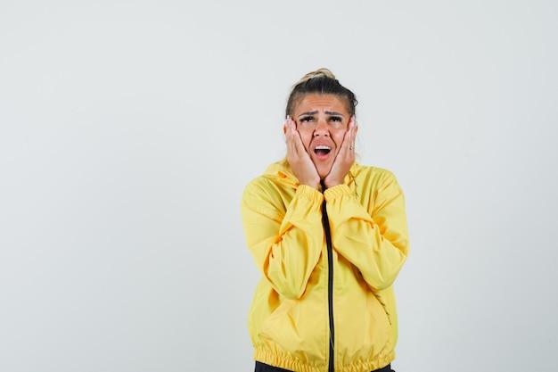 Kobieta w sportowym garniturze, trzymając dłonie na policzkach i patrząc żałośnie, z przodu.
