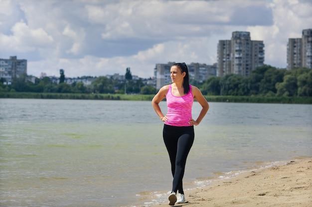 Kobieta w sportowym mundurze podchodzi do jeziora