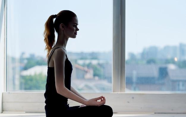 Kobieta w sportowym mundurze w pobliżu okna fitness ćwiczenia medytacja