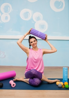 Kobieta w sportowym stroju siedzi z piłkami do masażu na dywanie w studiu