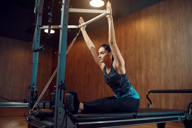 Kobieta w sprawnej robi ćwiczenia rozciągające pilates w siłowni. trening fitness w klubie sportowym. lekkoatletyczna osoba płci żeńskiej, aerobik