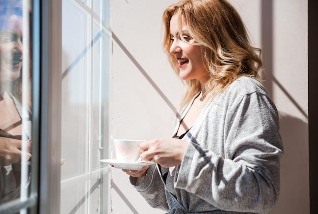 Kobieta w srebrnym szlafroku stoi przy oknie z kubkiem napoju w dłoniach