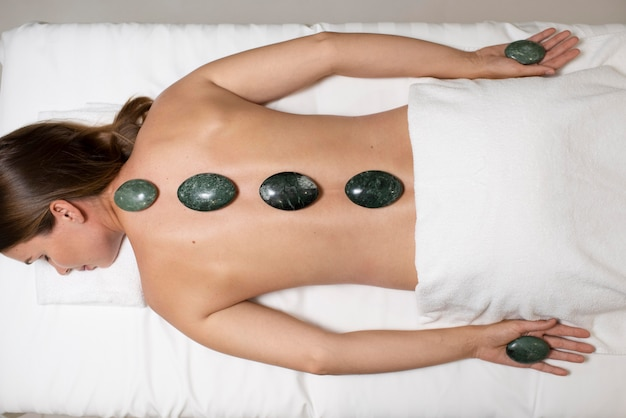 Kobieta w średnim ujęciu podczas zabiegu spa