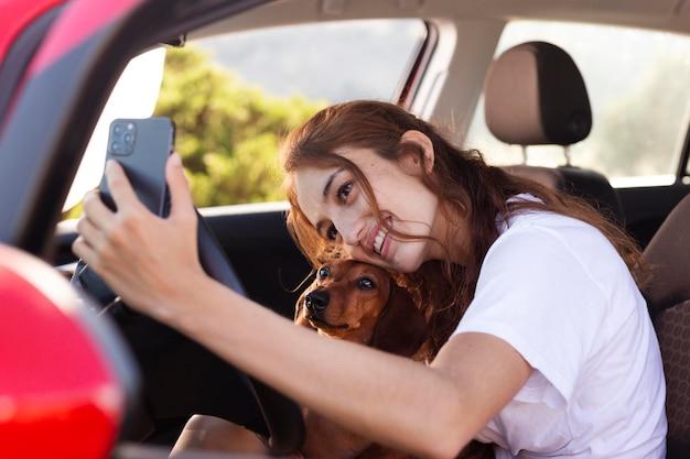Kobieta w średnim ujęciu robi selfie z psem
