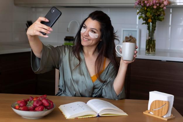 Kobieta w średnim ujęciu robi selfie