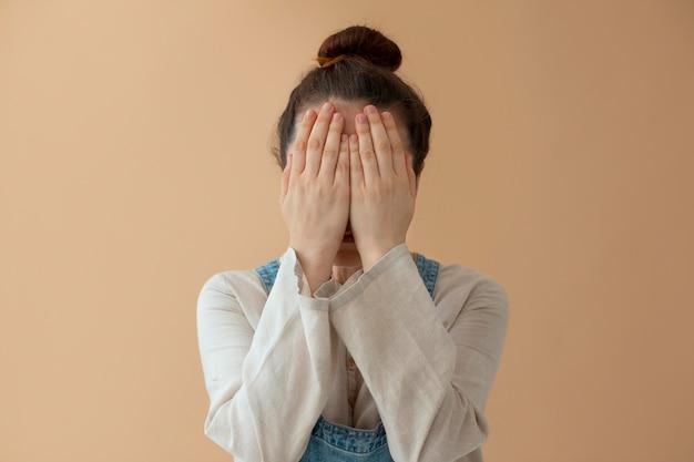 Kobieta w średnim ujęciu zakrywająca twarz