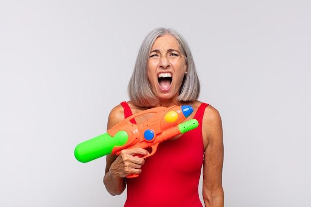 Kobieta w średnim wieku agresywnie krzycząca, wyglądająca na bardzo wściekłą, sfrustrowaną, oburzoną lub zirytowaną, krzycząca nie z pistoletu na wodę