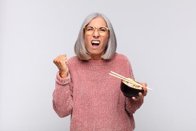 Kobieta w średnim wieku agresywnie krzycząca z gniewnym wyrazem twarzy lub z zaciśniętymi pięściami świętuje sukces koncepcji azjatyckiego jedzenia