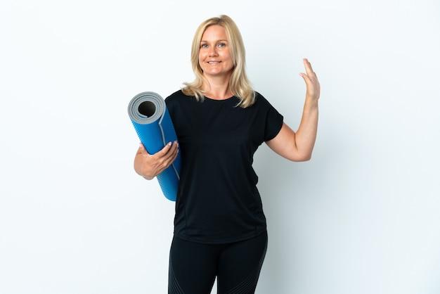 Kobieta w średnim wieku będzie na zajęcia jogi, trzymając matę na białym tle na białej ścianie, salutując ręką z happy wypowiedzi