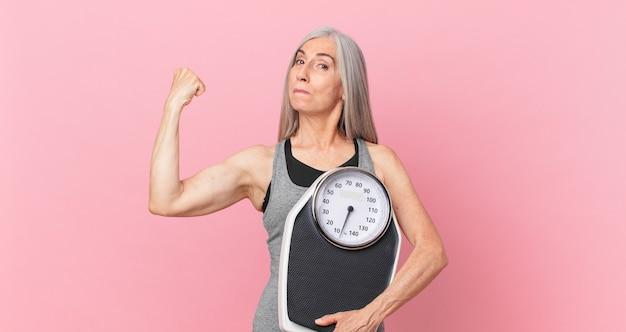 Kobieta w średnim wieku, białe włosy, trzymając wagę. koncepcja fitness i diety
