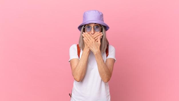 Kobieta w średnim wieku, białe włosy, zakrywając usta rękami z szoku. koncepcja lato