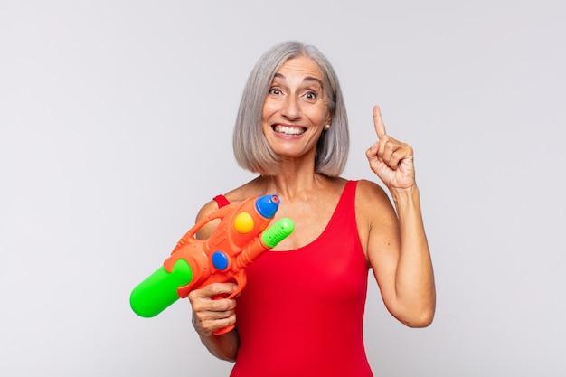 Kobieta w średnim wieku czując się jak szczęśliwy i podekscytowany geniusz po zrealizowaniu pomysłu, radośnie podnosząc palec, eureka! z pistoletem na wodę