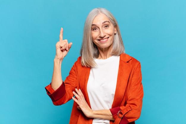 Kobieta w średnim wieku czując się jak szczęśliwy i podekscytowany geniusz po zrealizowaniu pomysłu, radośnie podnosząc palec, eureka!