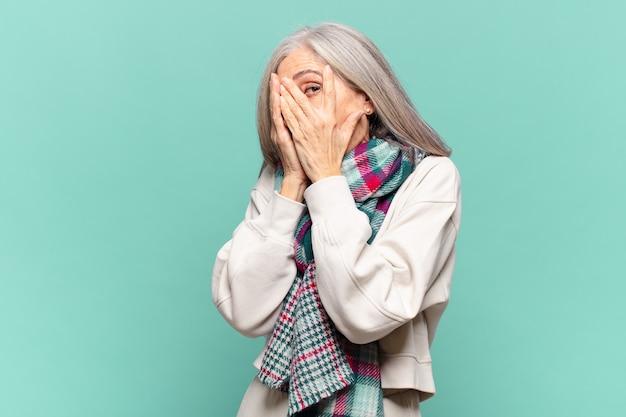 Kobieta w średnim wieku czująca się przestraszona lub zawstydzona, zerkająca lub szpiegująca z oczami do połowy zasłoniętymi dłońmi