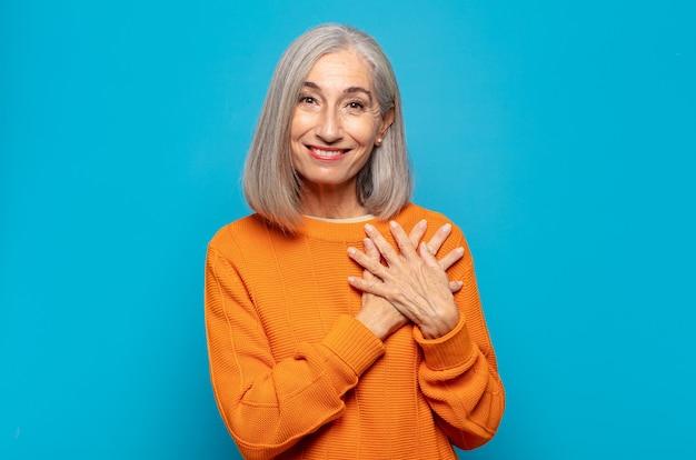 Kobieta w średnim wieku czująca się romantycznie, szczęśliwa i zakochana, uśmiechnięta radośnie i trzymająca się za ręce blisko serca