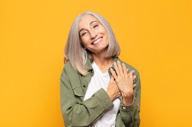 Kobieta w średnim wieku czująca się romantycznie, szczęśliwa i zakochana, uśmiechnięta wesoło i trzymająca się za ręce blisko serca