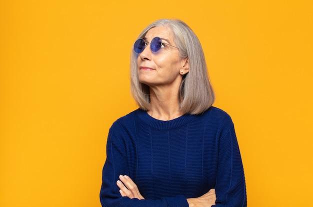 Kobieta w średnim wieku czująca się szczęśliwa, dumna i pełna nadziei, zastanawiająca się lub myśląca, spoglądająca w górę, aby skopiować przestrzeń ze skrzyżowanymi rękami