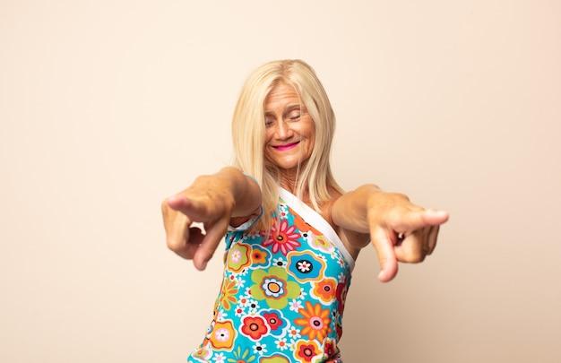 Kobieta w średnim wieku czująca się szczęśliwa i pewna siebie, wskazująca na aparat obiema rękami i śmiejąca się, wybierając ciebie