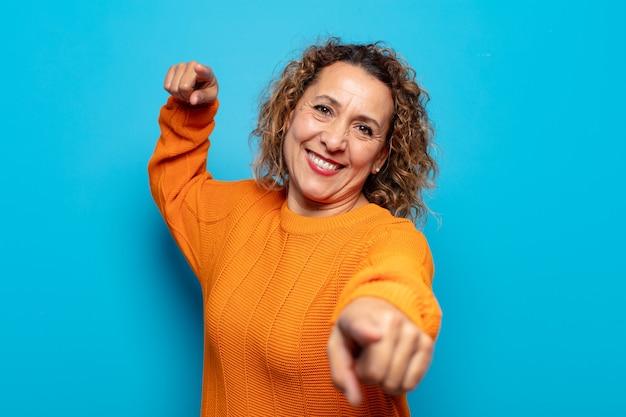 Kobieta w średnim wieku czująca się szczęśliwa i pewna siebie, wskazująca przed siebie obiema rękami i śmiejąca się, wybierając ciebie