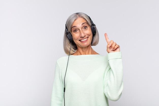 Kobieta w średnim wieku czująca się szczęśliwą i podekscytowaną geniuszką po zrealizowaniu pomysłu, radośnie podnosząca palec, eureka!