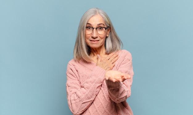 Kobieta w średnim wieku czująca się szczęśliwa i zakochana, uśmiechająca się z jedną ręką obok serca, a drugą wyciągniętą do przodu