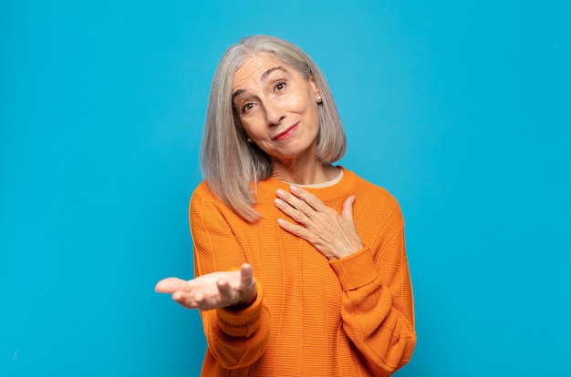 Kobieta w średnim wieku czująca się szczęśliwa i zakochana, uśmiechnięta z jedną ręką obok serca, a drugą wyciągniętą do przodu