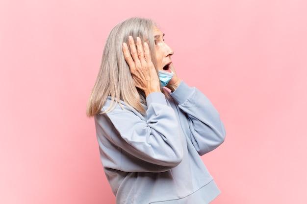 Kobieta w średnim wieku czująca się szczęśliwa, podekscytowana i zaskoczona, patrząc w bok z obiema rękami na twarzy