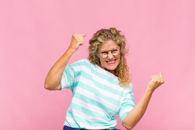Kobieta w średnim wieku czująca się szczęśliwa, pozytywna i odnosząca sukcesy, świętująca zwycięstwo, osiągnięcia lub powodzenia