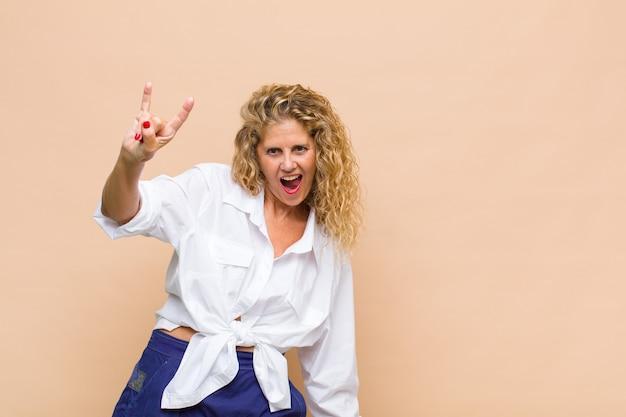 Kobieta w średnim wieku czująca się szczęśliwa, wesoła, pewna siebie, pozytywna i buntownicza, wykonująca ręką rockowy lub heavy metalowy znak