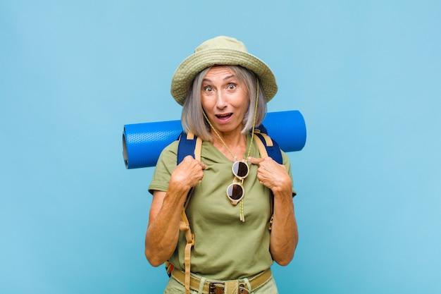 Kobieta w średnim wieku czująca się szczęśliwa, zdziwiona i dumna, wskazująca na siebie z podekscytowanym, zdumionym spojrzeniem