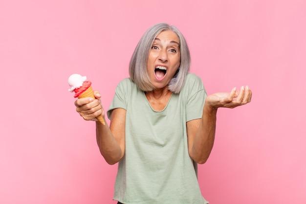 Kobieta w średnim wieku czująca się wyjątkowo zszokowana i zaskoczona, niespokojna i spanikowana, ze zestresowanym i przerażonym spojrzeniem, mająca lody