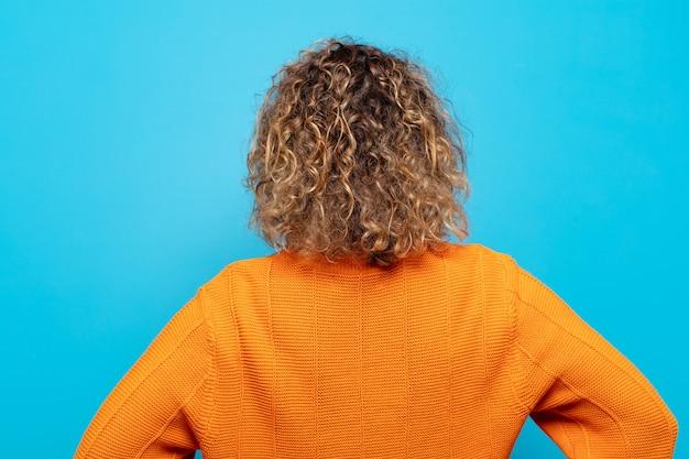 Kobieta w średnim wieku czująca się zagubiona lub pełna lub wątpliwości i pytania, zastanawiająca się, z rękami na biodrach, widok z tyłu