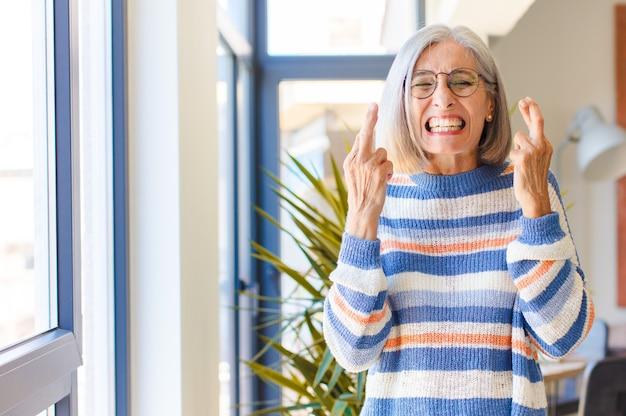 Kobieta w średnim wieku czująca się zdenerwowana i pełna nadziei, trzymająca kciuki, modląca się i licząca na szczęście