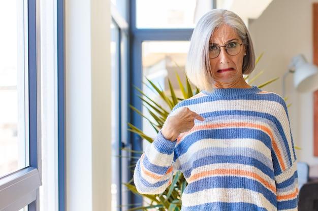 Kobieta w średnim wieku czująca się zdezorientowana, zdziwiona i niepewna, wskazuje na to, że się zastanawia i pyta kogo, ja?