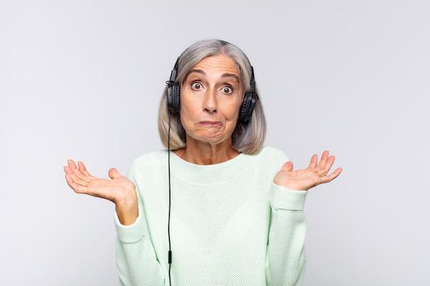 Kobieta w średnim wieku czująca się zdziwiona i zdezorientowana, wątpiąca, ważąca lub wybierając różne opcje z zabawnym wyrazem twarzy. koncepcja muzyki