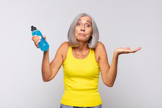 Kobieta w średnim wieku czująca się zdziwiona i zdezorientowana, wątpiąca, ważąca lub wybierając różne opcje z zabawnym wyrazem twarzy