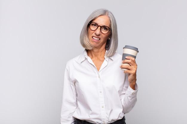 Kobieta w średnim wieku czująca się zdziwiona i zdezorientowana, z głupim, oszołomionym wyrazem twarzy, patrząc na coś nieoczekiwanego koncepcję kawy