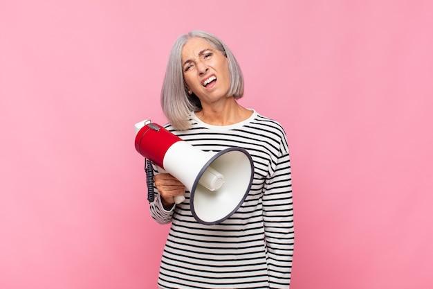 Kobieta w średnim wieku czująca się zdziwiona i zdezorientowana, z głupim, oszołomionym wyrazem twarzy, patrząc na coś nieoczekiwanego przez megafon
