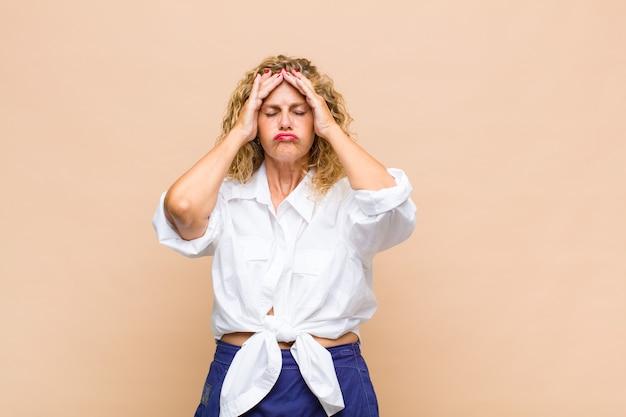 Kobieta w średnim wieku czująca się zestresowana i niespokojna, przygnębiona i sfrustrowana bólem głowy, podnosząca obie ręce do głowy