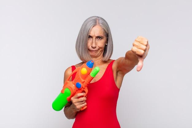 Kobieta w średnim wieku czująca się zła, zła, zirytowana, rozczarowana lub niezadowolona, pokazująca kciuki w dół z poważnym spojrzeniem pistoletem na wodę