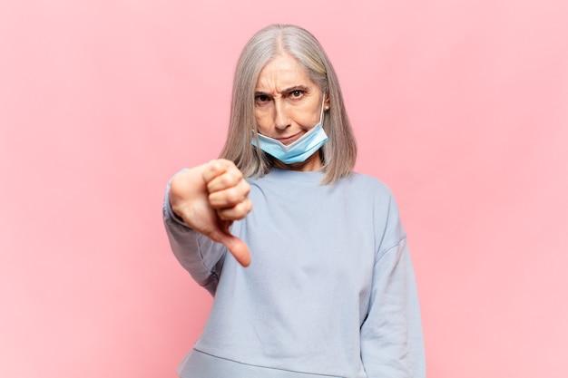 Kobieta w średnim wieku czująca się zła, zła, zirytowana, rozczarowana lub niezadowolona, pokazująca kciuki w dół z poważnym spojrzeniem
