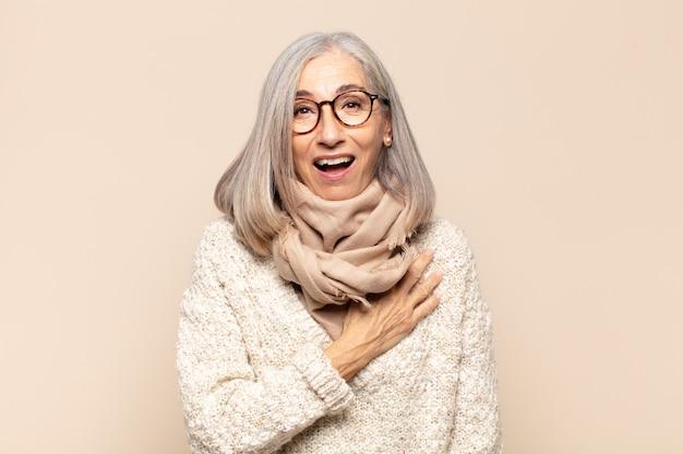 Kobieta w średnim wieku czująca się zszokowana i zdziwiona, uśmiechnięta, biorąca się za serce, szczęśliwa, że jest tą jedyną lub okazująca wdzięczność