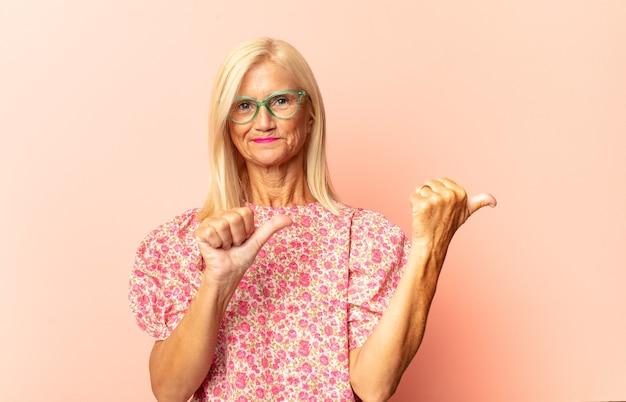 Kobieta w średnim wieku czująca się zszokowana, szczęśliwa, zdumiona i zdziwiona, patrzy w bok z otwartymi ustami
