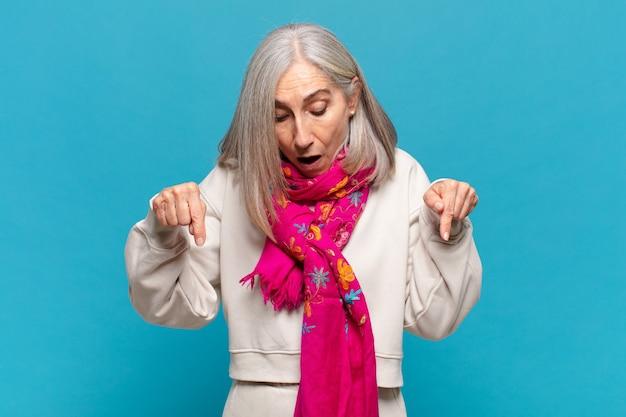 Kobieta w średnim wieku czująca się zszokowana, z otwartymi ustami i zdumieniem, patrząca w dół z niedowierzaniem i zdziwieniem