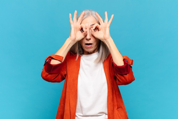 Kobieta w średnim wieku czująca się zszokowana, zdumiona i zdziwiona, trzymająca okulary ze zdumieniem i niedowierzaniem