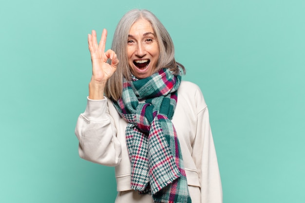 Kobieta w średnim wieku czująca sukces i zadowolona, uśmiechnięta z szeroko otwartymi ustami, robiąca dobry znak ręką