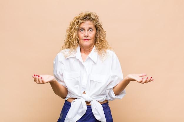 Kobieta w średnim wieku czuje się niepewna i zdezorientowana, nie jest pewna, który wybór lub opcję wybrać, zastanawiając się